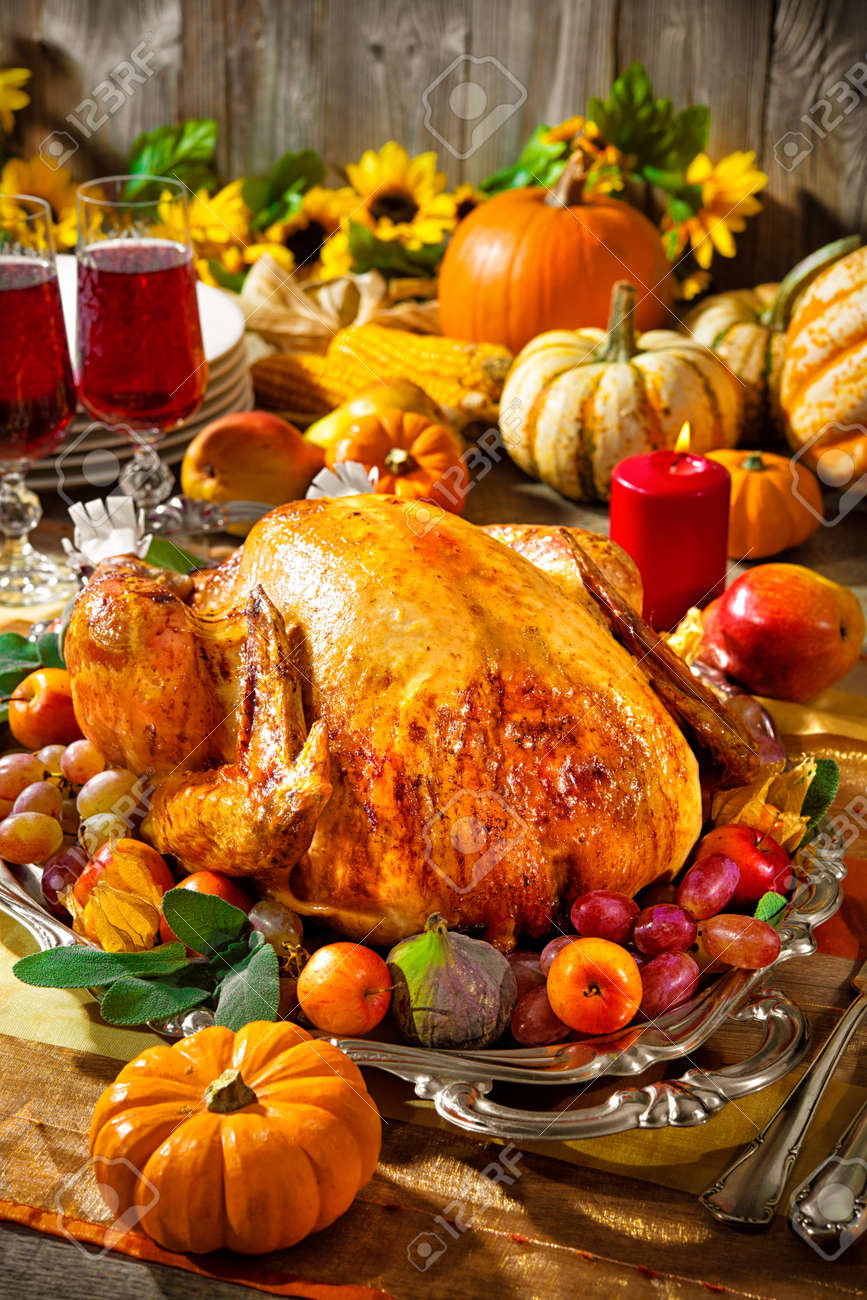 Thanksgiving dinner. Roasted turkey on holiday table with pumpkins, flowers and wine Stock Photo - 47931599