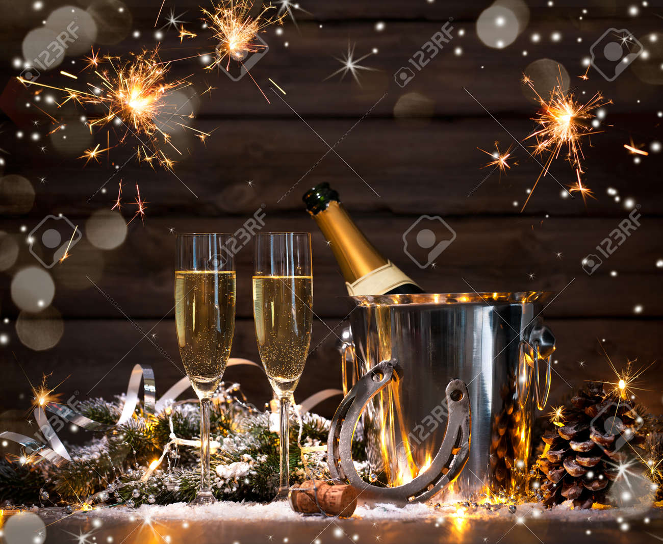 New Years Eve celebration background with pair of flutes and bottle of champagne in bucket and a horseshoe as lucky charm Stock Photo - 50199449
