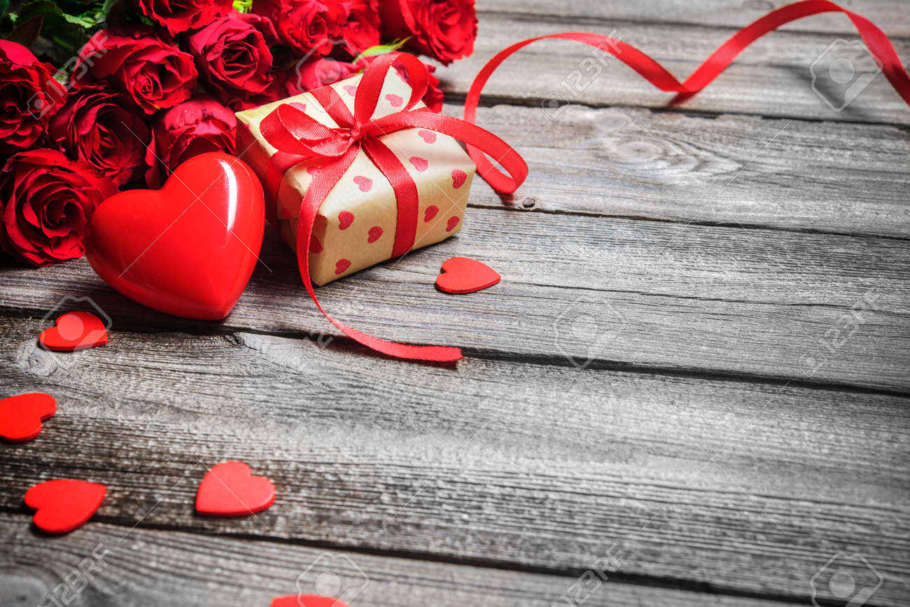 Valentines day vintage background with heart, red roses and gift box on wooden board - 50773354