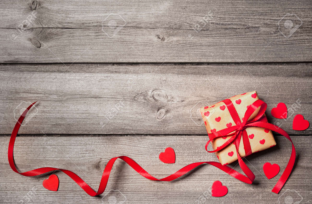 Valentines day vintage background with hearts and a gift box on wooden board Stock Photo - 50773387