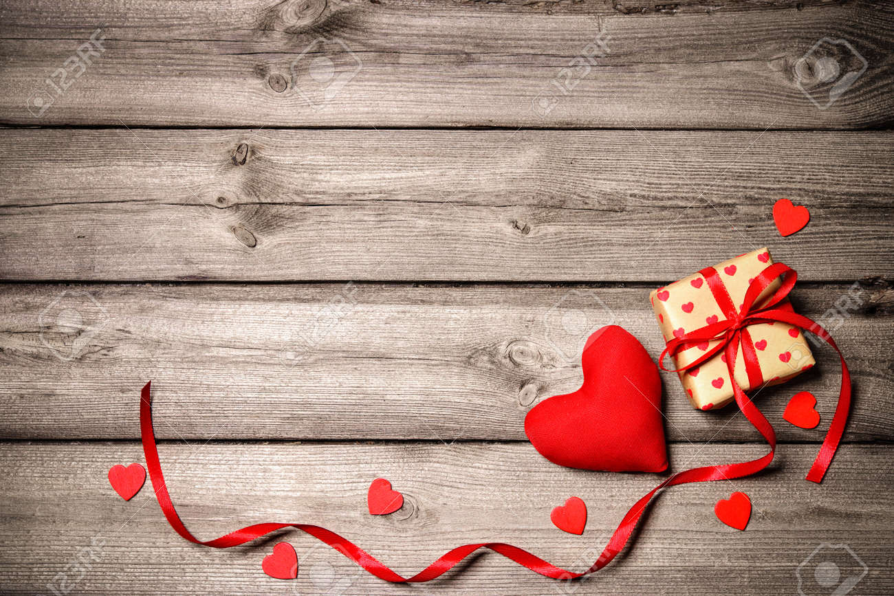 Valentines day vintage background with hearts and a gift box on wooden board Stock Photo - 50773400