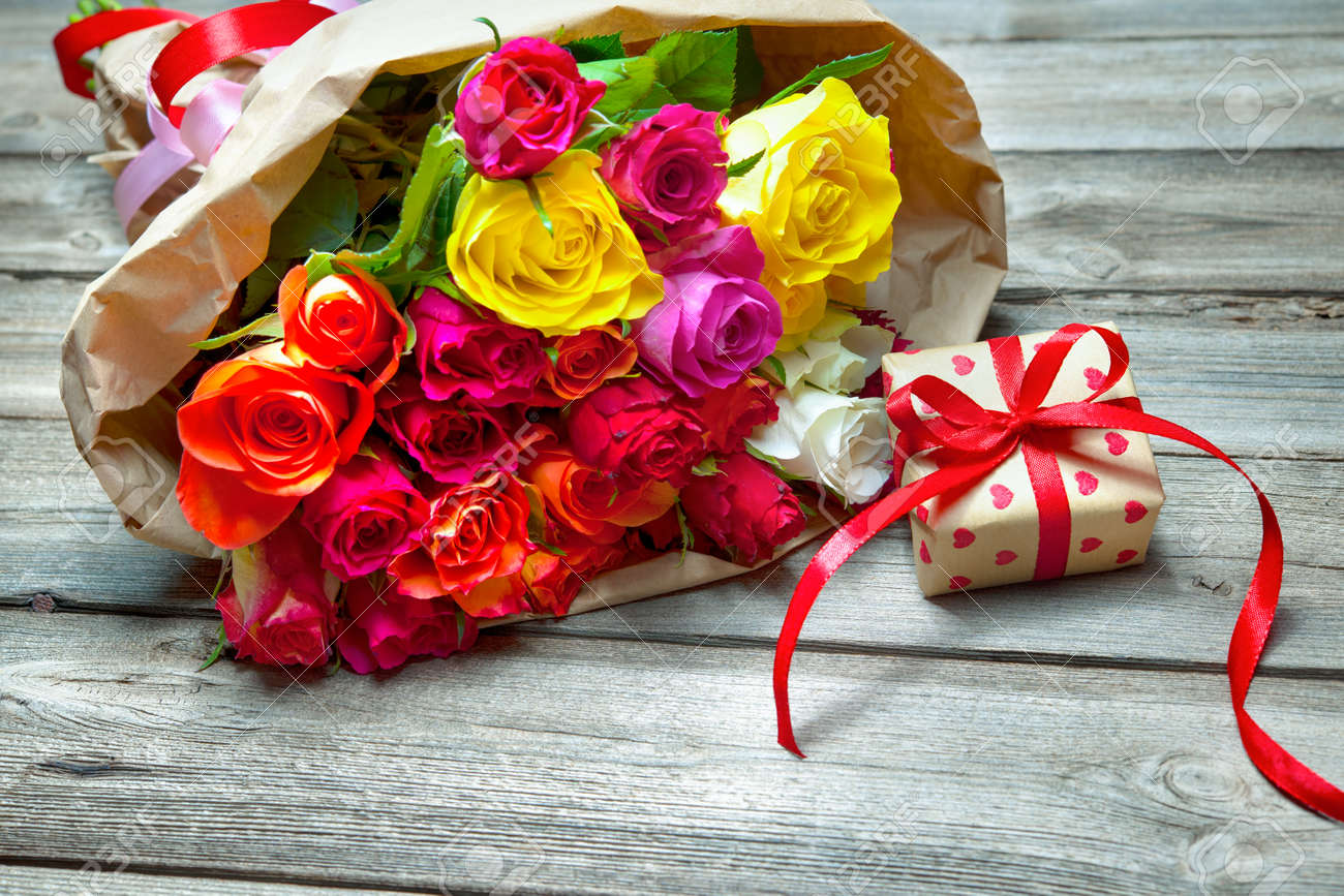 Background with bouquet of roses and gift box on wooden board Stock Photo - 50773403