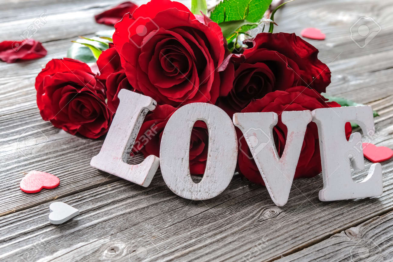 Red roses flowers and word love on wooden background