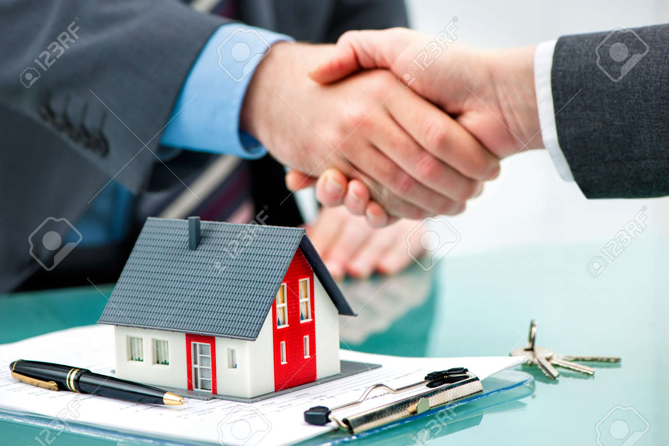 Estate agent shaking hands with customer after contract signature Stock Photo - 52326000