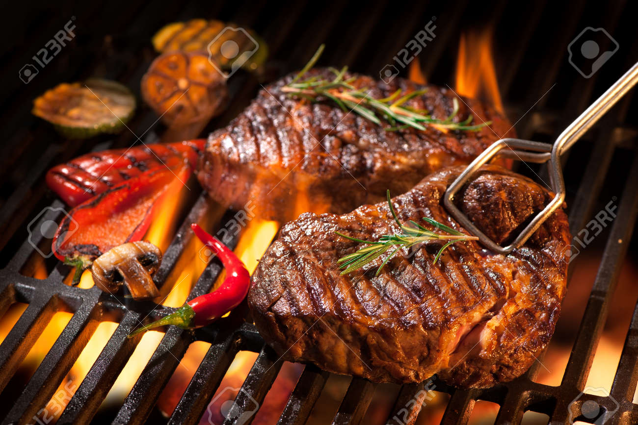Beef steaks on the grill with flames - 52913995