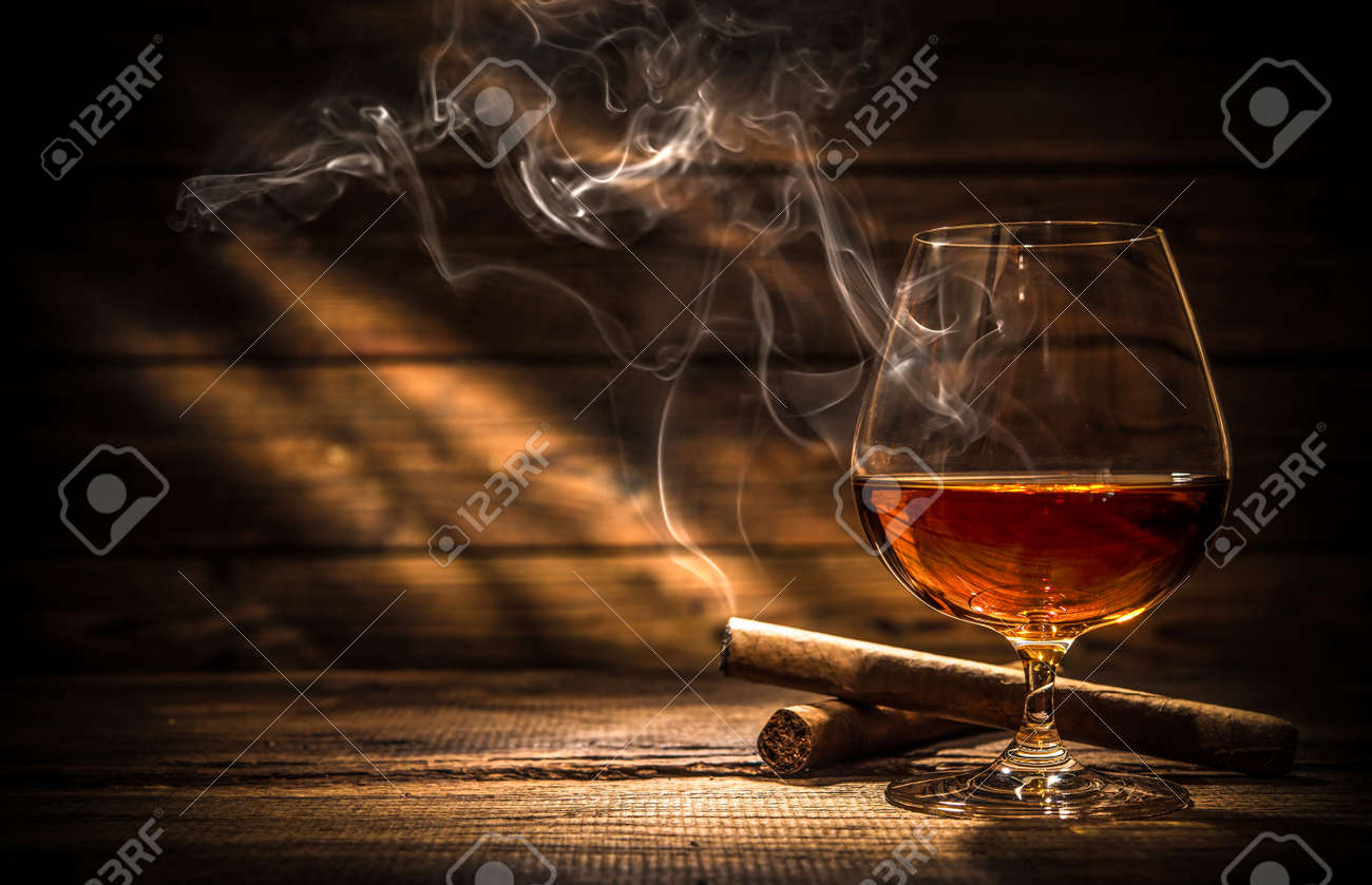 Glass of whiskey with smoking cigar and ice cubes on wooden table Stock Photo - 54094133