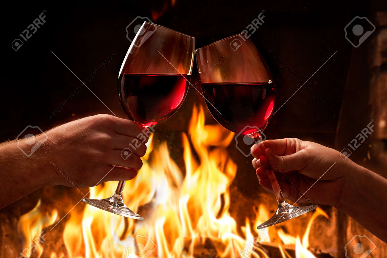 Hands toasting wine glasses in front of lit fireplace Stock Photo - 54094155