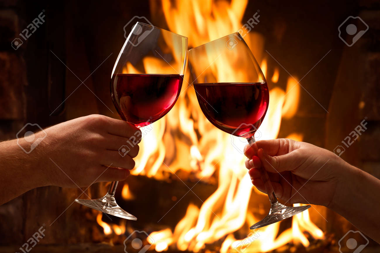 Hands toasting wine glasses in front of lit fireplace - 54094181