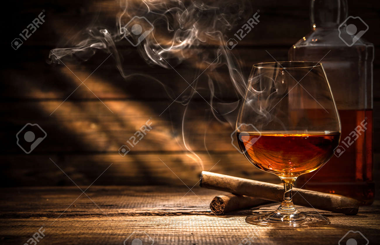 Glass of whiskey with smoking cigar and ice cubes on wooden table Stock Photo - 54094203