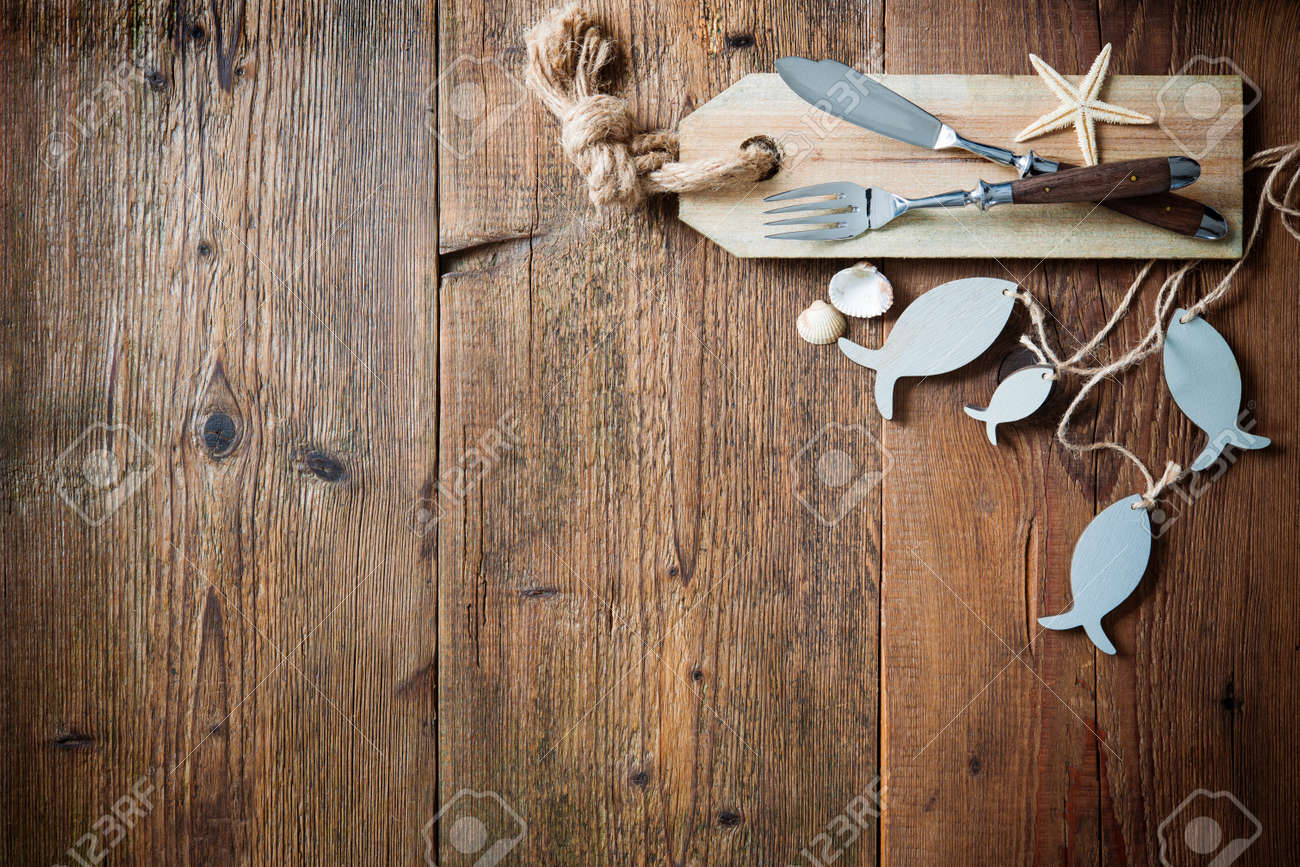 Fish Cutlery Tied With Empty Fish Shaped Tag On Wooden Table With Copy  Space. Menu