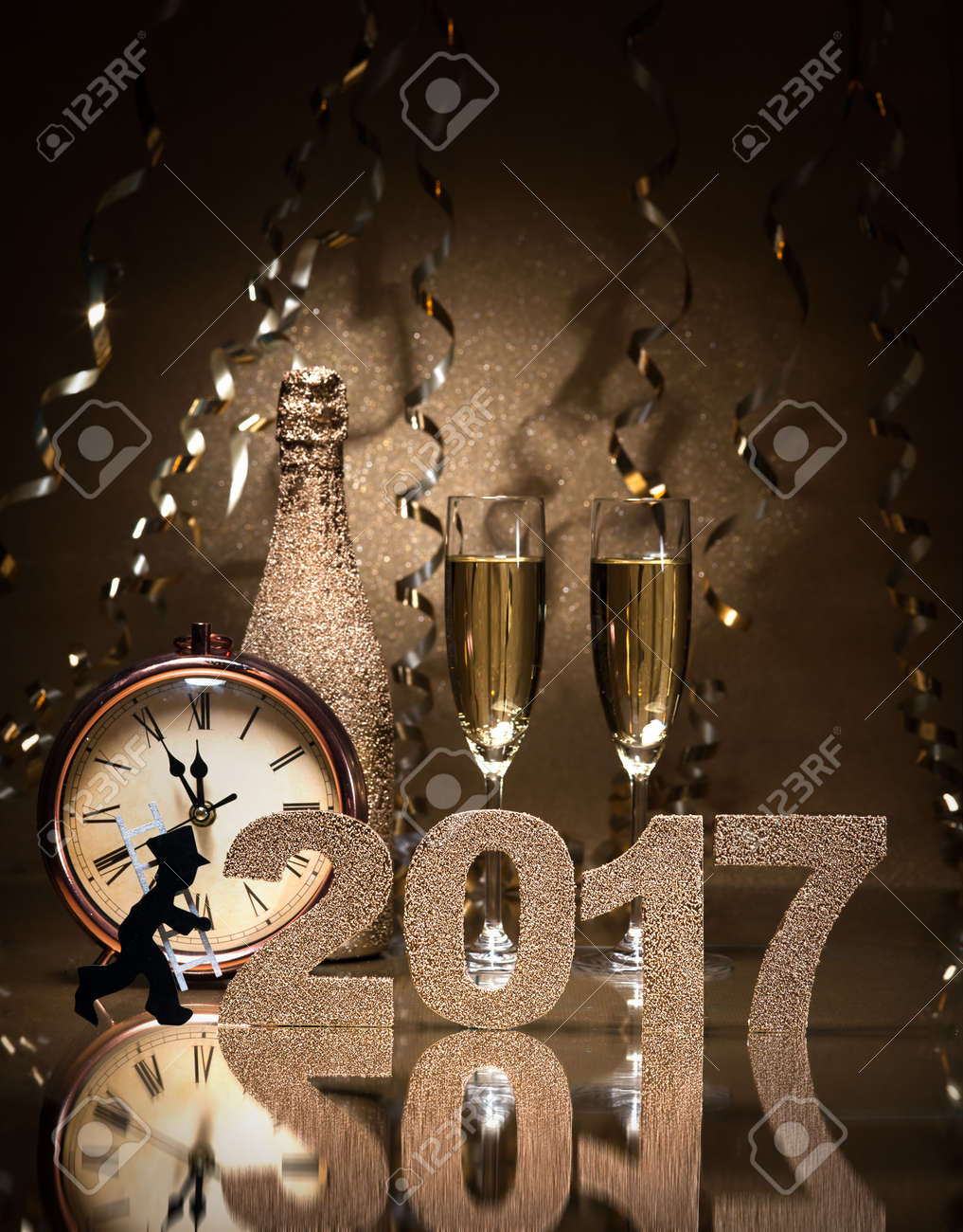 New Years Eve celebration background with pair of flutes, bottle of champagne, clock and a chimney sweep as lucky charm Stock Photo - 57246676