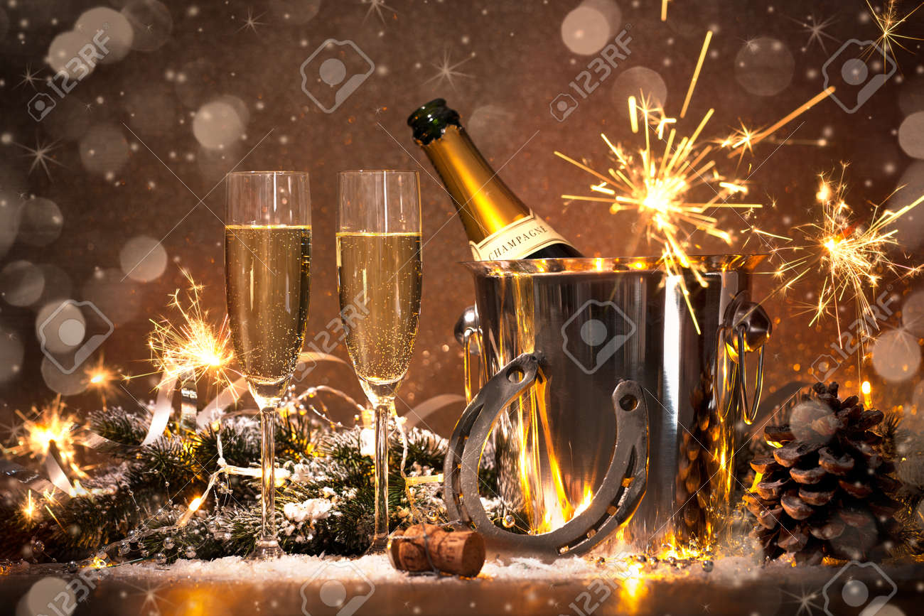 New Years Eve celebration background with pair of flutes and bottle of champagne in  bucket  and a horseshoe as lucky charm Stock Photo - 57806495
