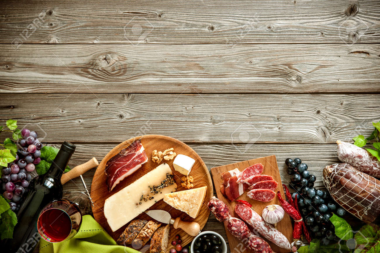 Wine bottles with grapes, cheese and traditional sausages on wooden background with copy space Stock Photo - 57807069
