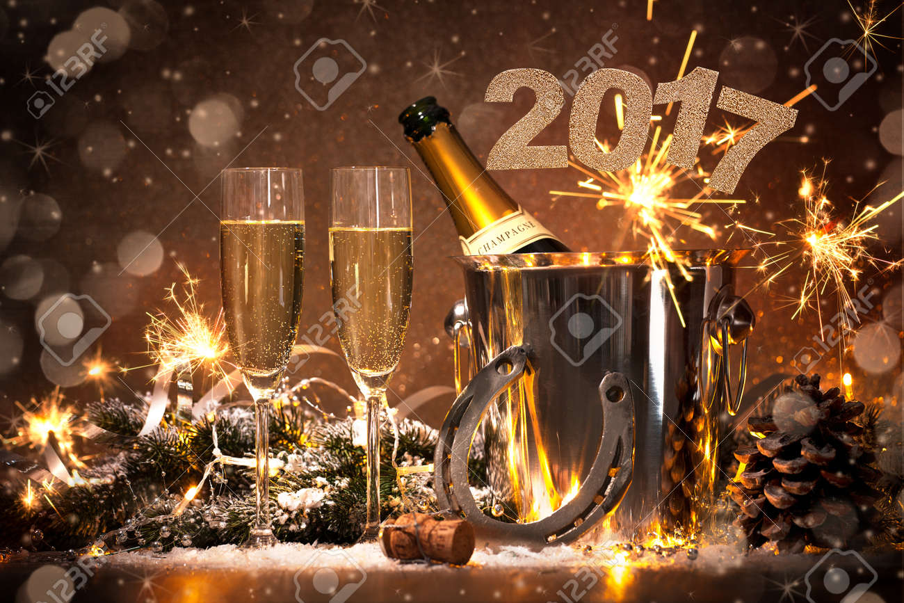 New Years Eve celebration background with pair of flutes and bottle of champagne in  bucket  and a horseshoe as lucky charm Stock Photo - 58713627