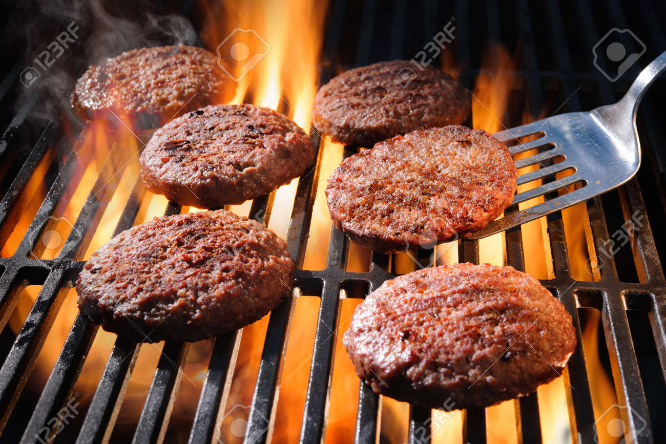 Juicy beef hamburger patties sizzling over hot flames on the barbecue - 63981886
