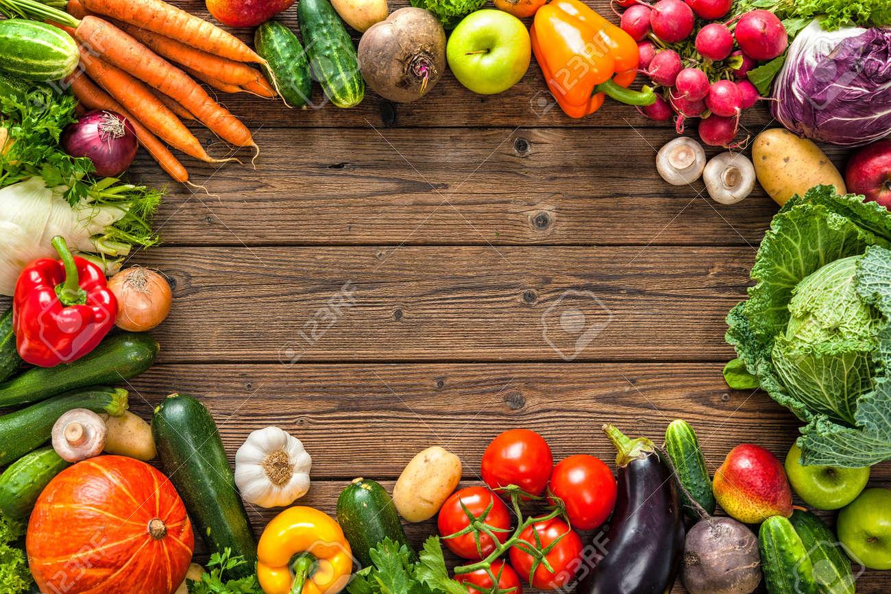Frame of assorted fresh vegetables on wooden background - 61924717