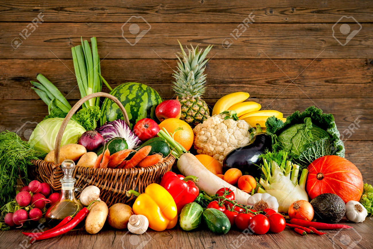 Assortment of the fresh fruits and vegetables on wooden background - 61924729