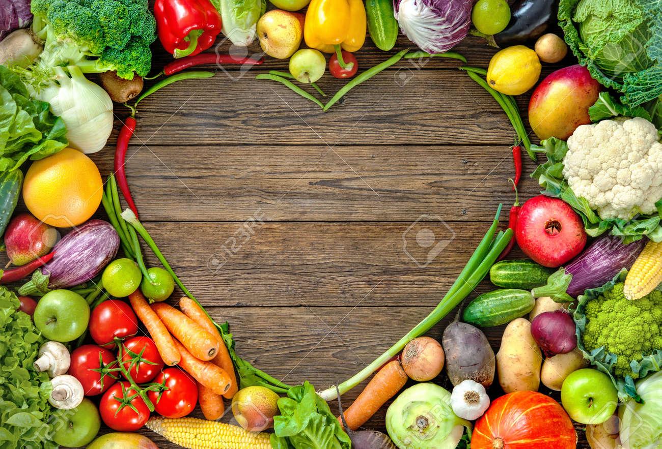 4d9603c87eb7 Surtido de frutas y verduras frescas en forma de corazón en el fondo de  madera