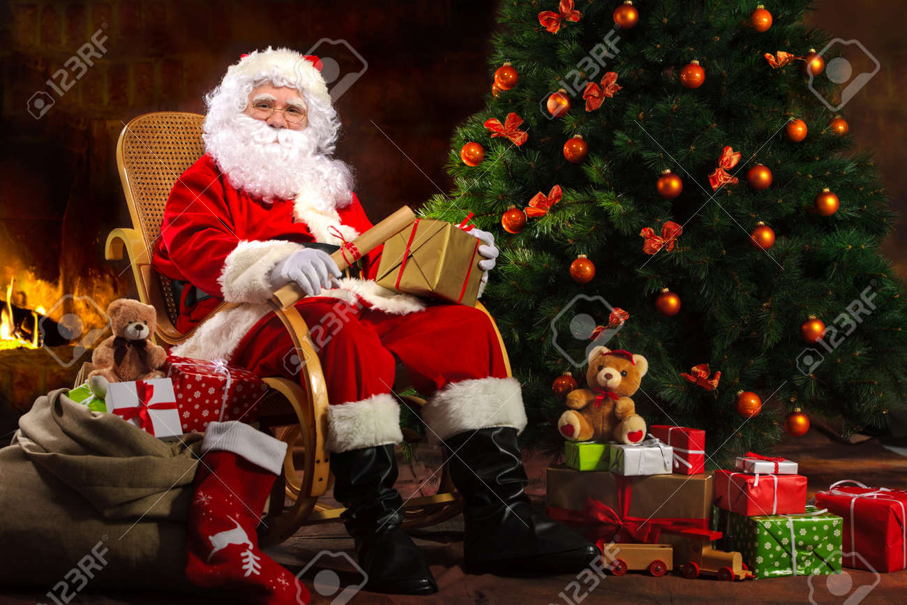 santa claus sitting in front of fireplace near christmas tree