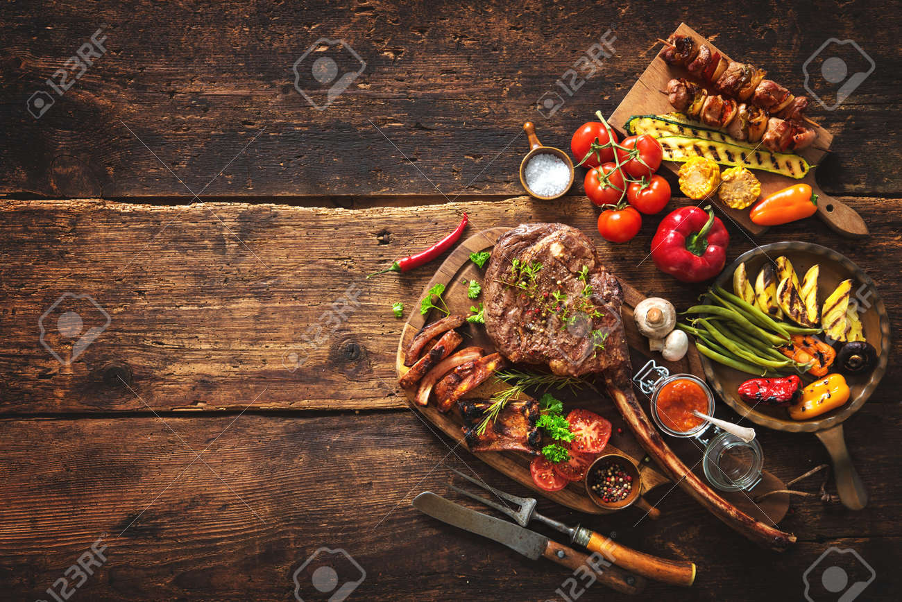 Grilled meat and vegetables on rustic wooden table - 76548404