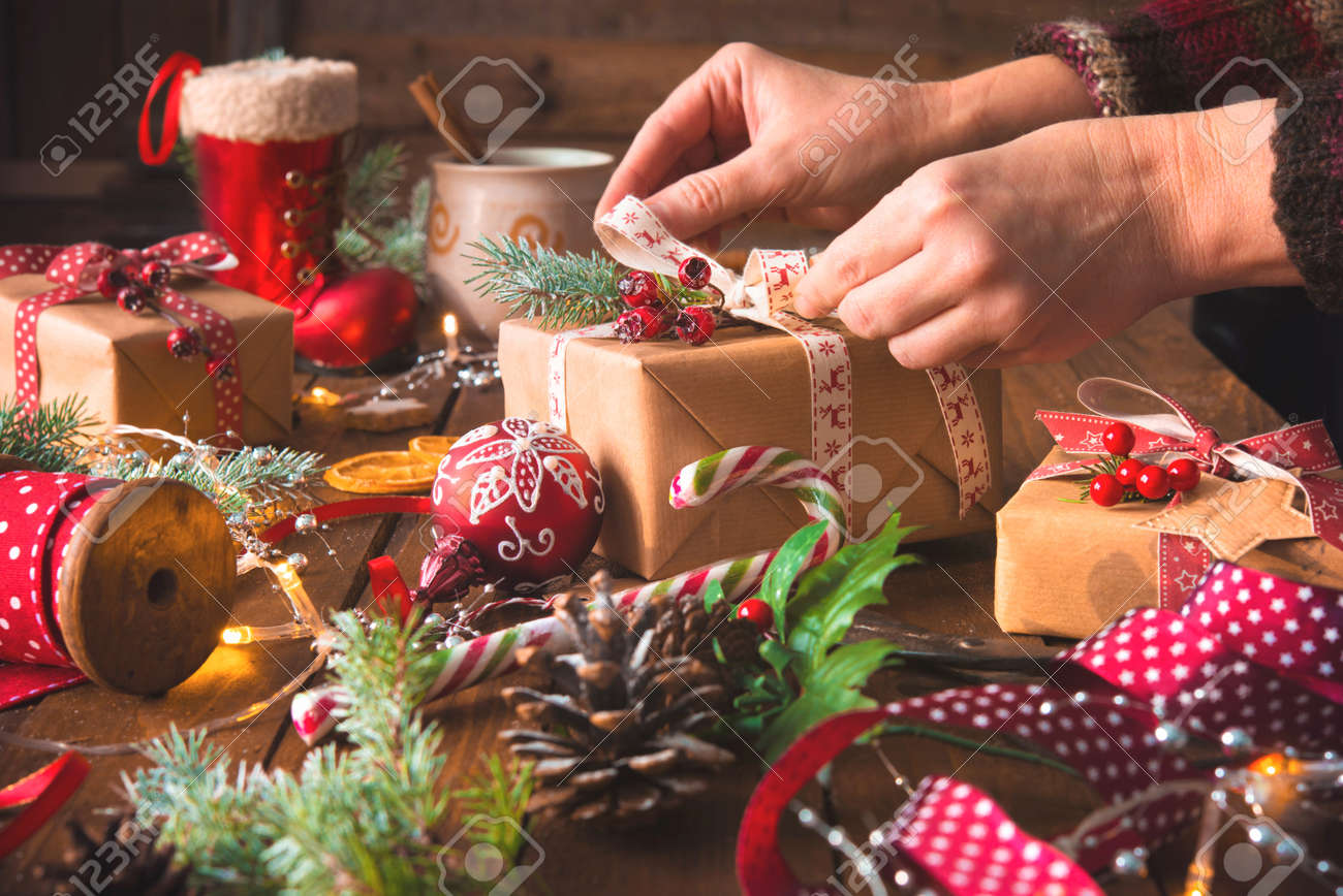 Female hands wrapping christmas holiday handmade presents in craft paper with ribbon on wooden table. Top view - 87180632
