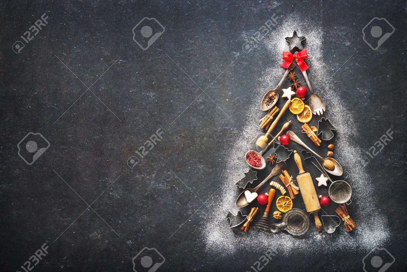 Christmas baking background with fir tree made from kitchen utensils, cookies, spices, cinnamon sticks, anise stars on rustic baking tray, top view - 88838285