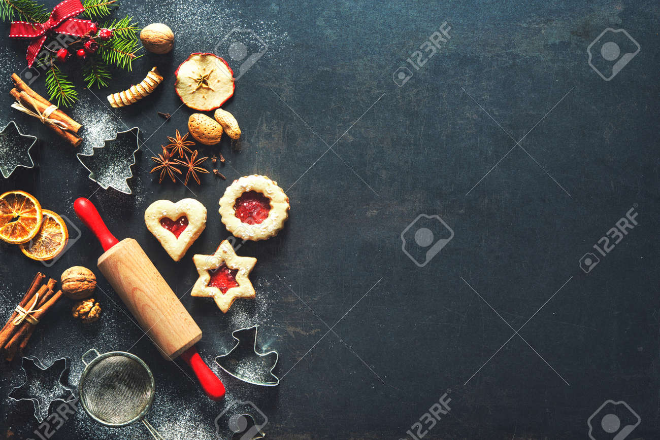 Christmas baking sweet food background with homemade cookies, spices, kitchen utensils, fir branches and red holiday decoration on dark rustic baking tray. Top view - 88838385