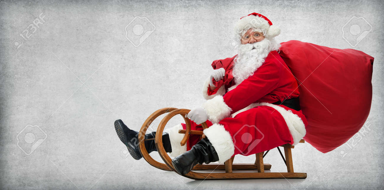 Santa Claus on his sledge with a bag full of Christmas gifts - 90057888