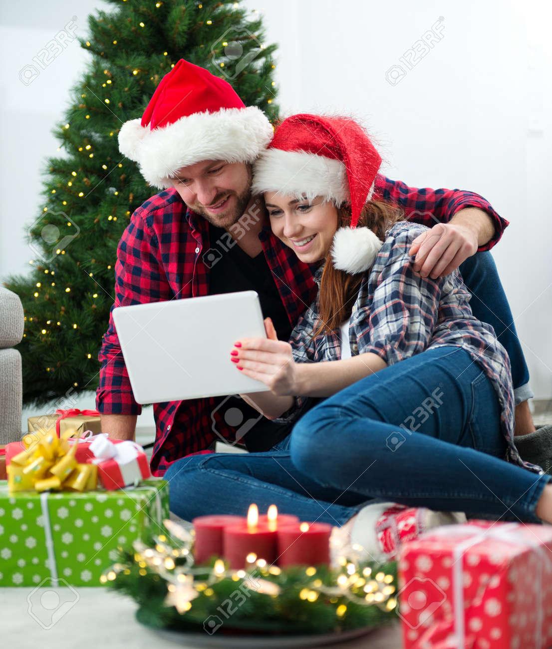 Junge Paare Mit Santa Claus-Hüten, Die On-line-Weihnachtsgeschenke ...