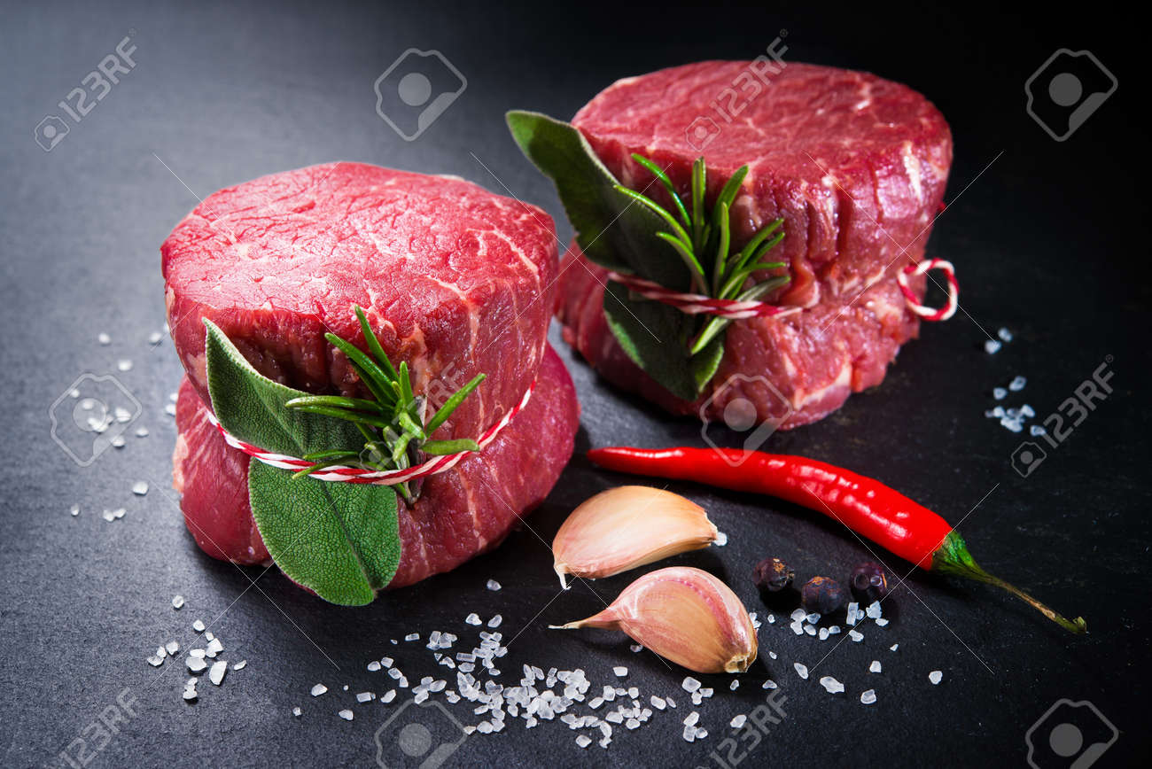 Raw beef fillet steaks mignon with spices on dark background - 96133669