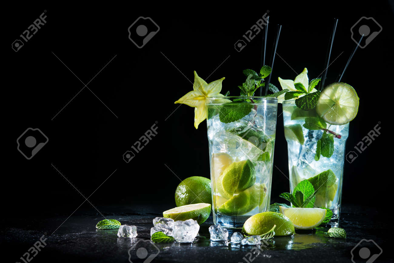 Two glasses of mojito cocktail with fresh lime and mint on a black stone board - 96072373