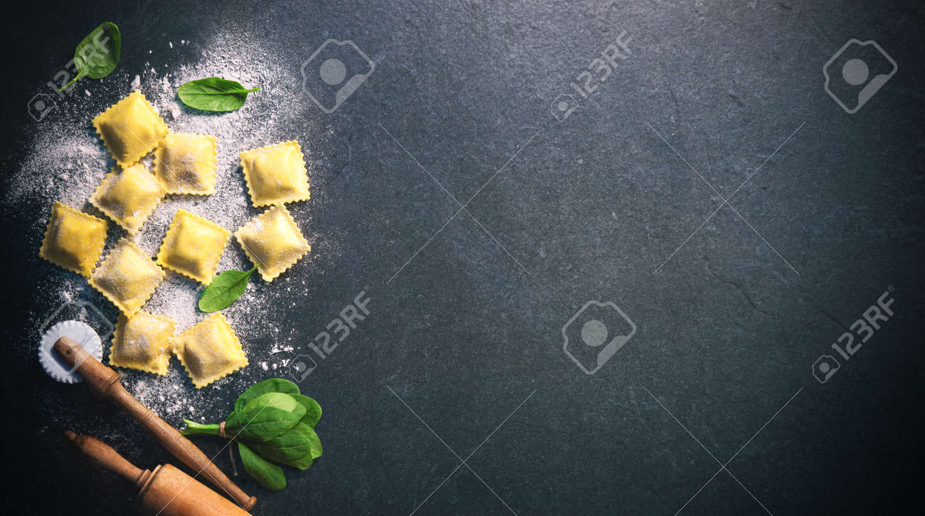 Ravioli with spinach and ricotta on dark background, top view - 96255003