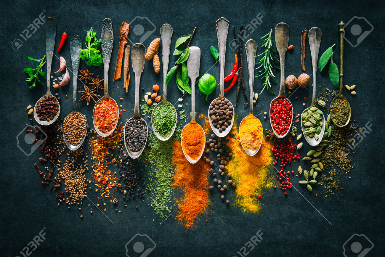 Colourful various herbs and spices for cooking on dark background - 99230322