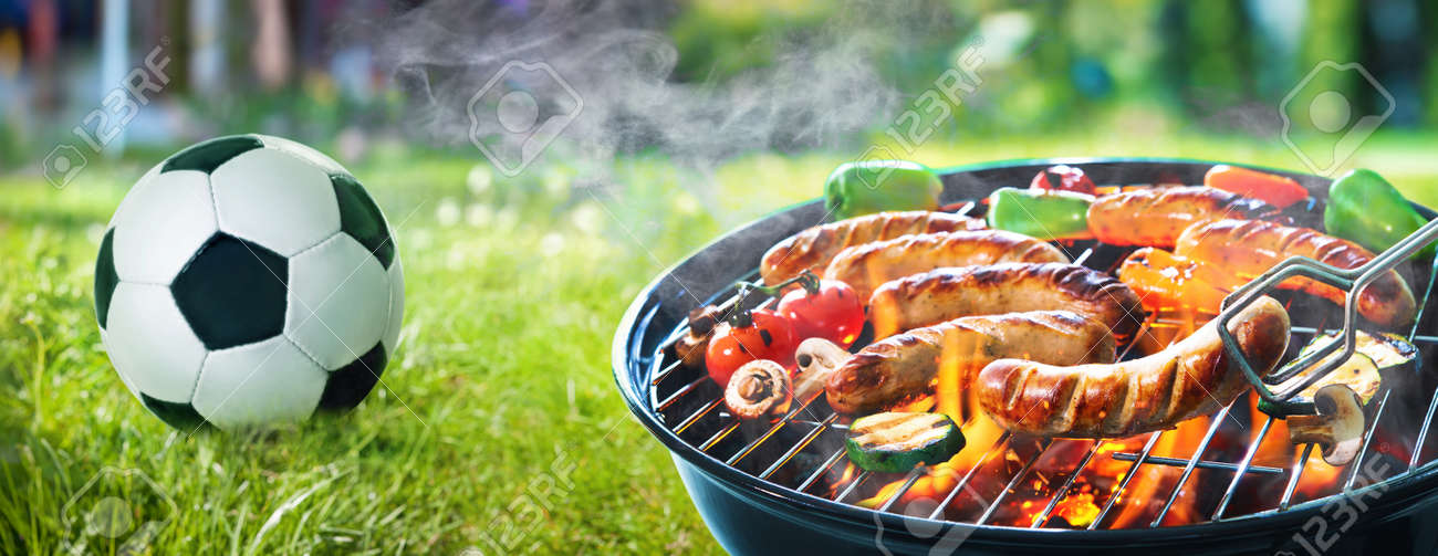 Picnic on a meadow with bratwurst on flaming grill and a soccer ball - 101962669