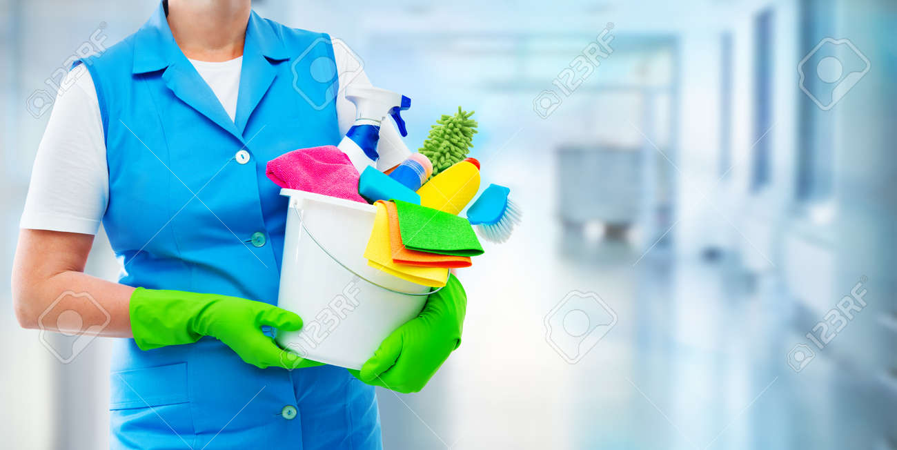 Female housekeeper while cleaning office. Woman wearing protective gloves and holding bucket full of cleaning supplies on blurred background - 103335276