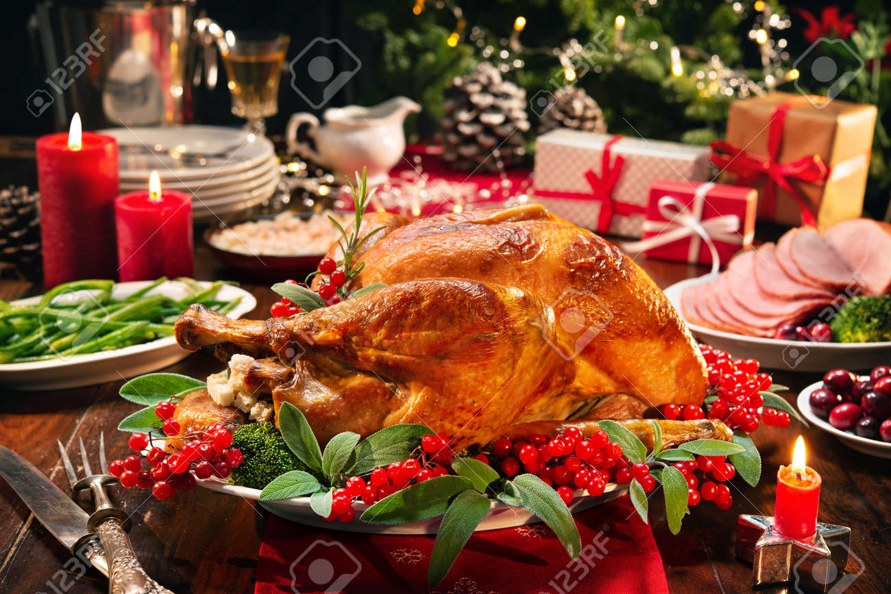 Christmas turkey dinner. Baked turkey garnished with red berries and sage leaves in front of Christmas tree and burning candles - 113928814