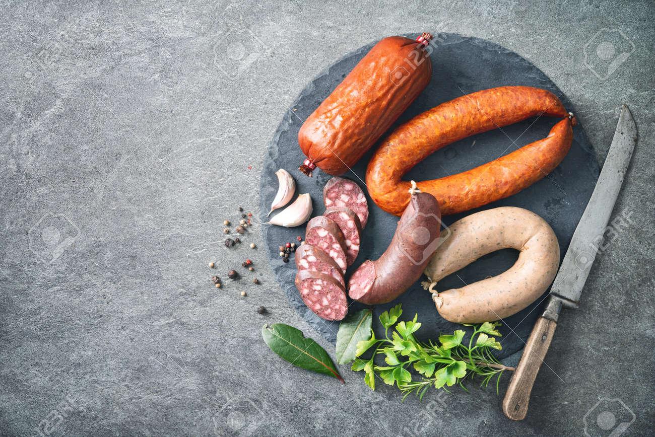 Assortment of german homemade sausage specialties: hard cured salami, liver sausage (Leberwurst), blood sausage (Blutwurst) and salami on kitchen table - 117666727