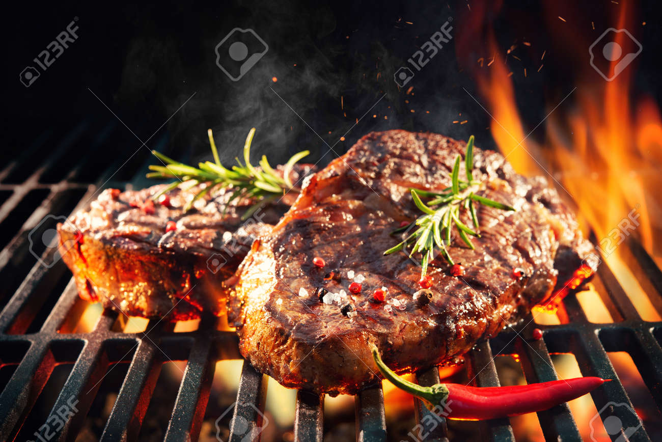 Beef steaks sizzling on the grill with flames - 120476345