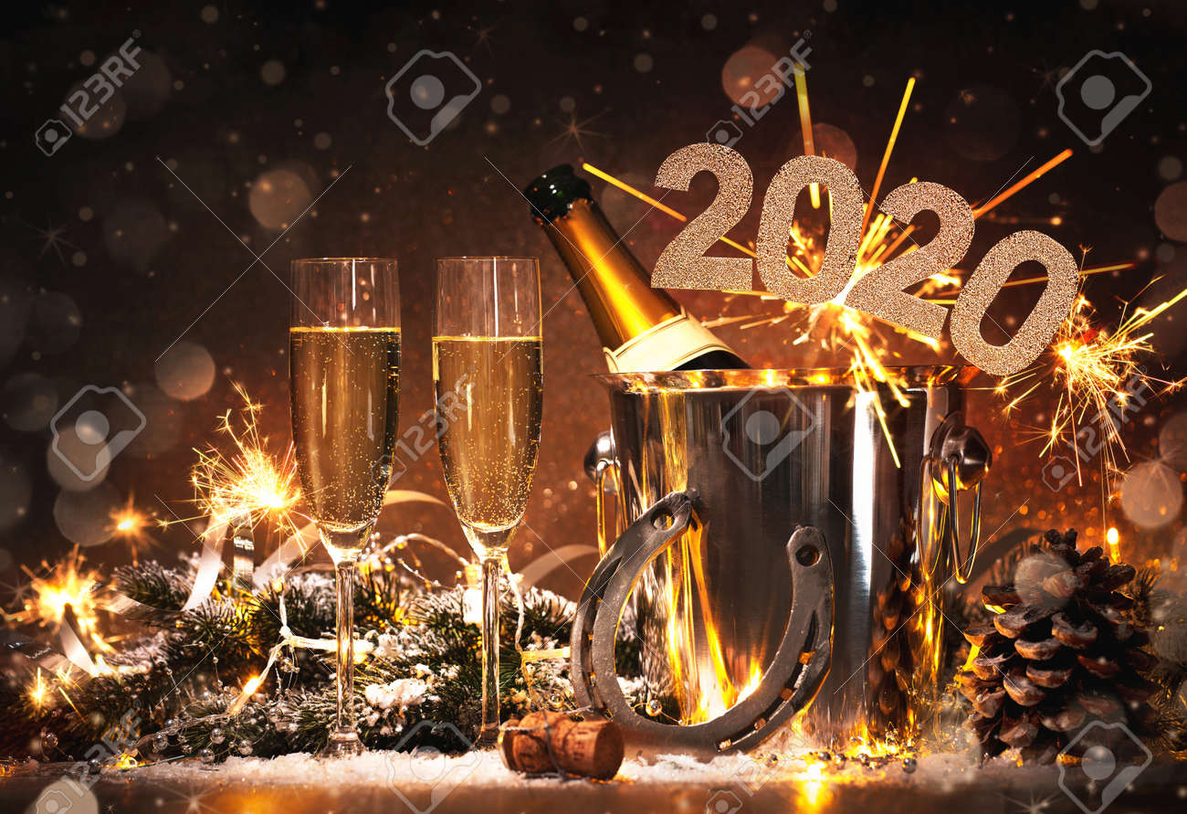 New Years Eve celebration background with pair of flutes and bottle of champagne in bucket and a horseshoe as lucky charm - 128483743
