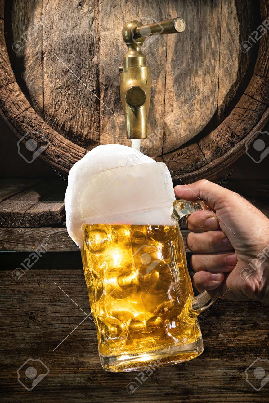 Hand Of Man Is Pouring A Large Lager Beer In Tap From Wooden
