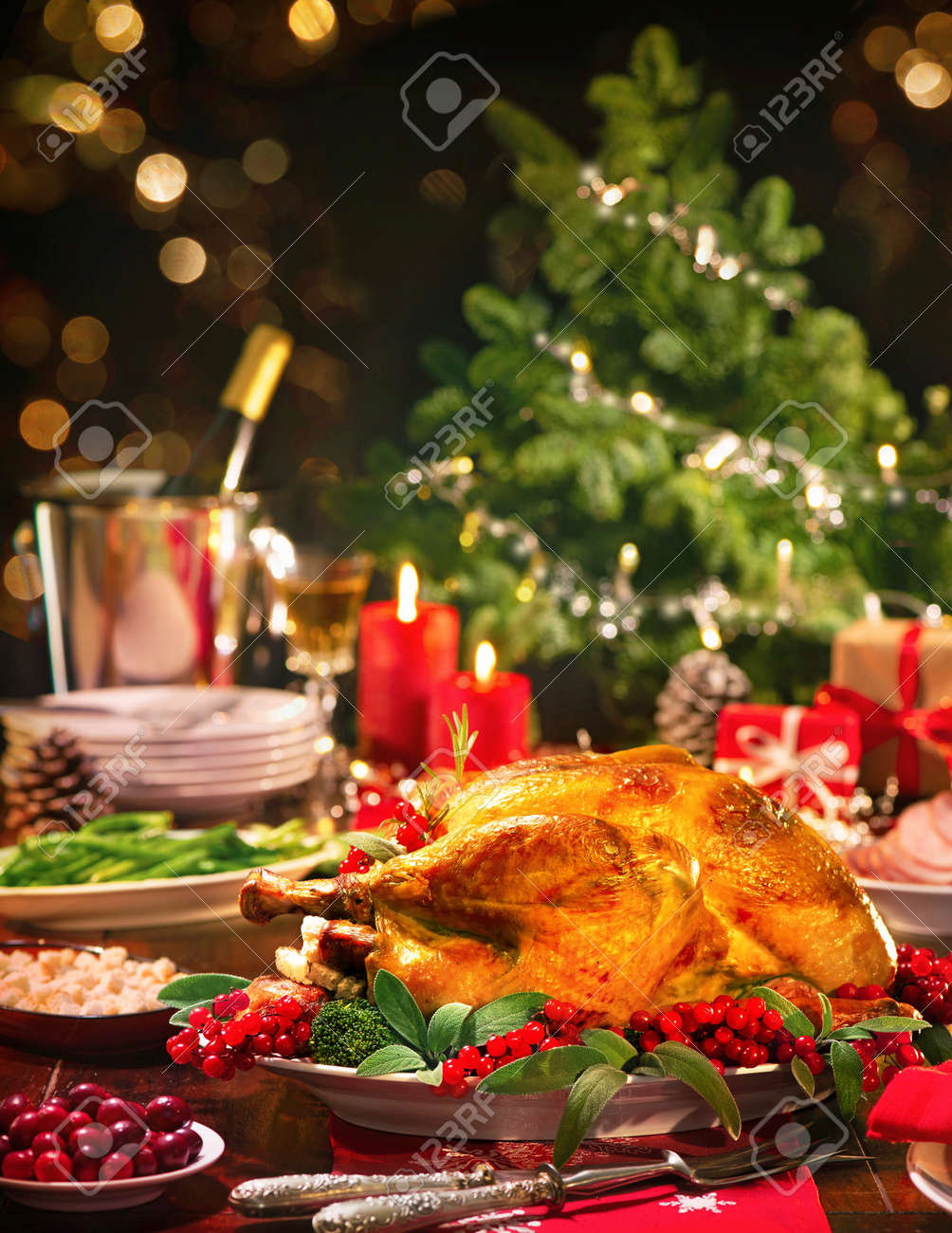 Christmas turkey dinner. Baked turkey garnished with red berries and sage leaves in front of Christmas tree and burning candles - 129613350