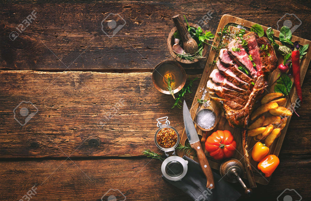 Grilled meat, sliced tomahawk beef steak with spices, french fries and vegetables on a rustic background - 145428945