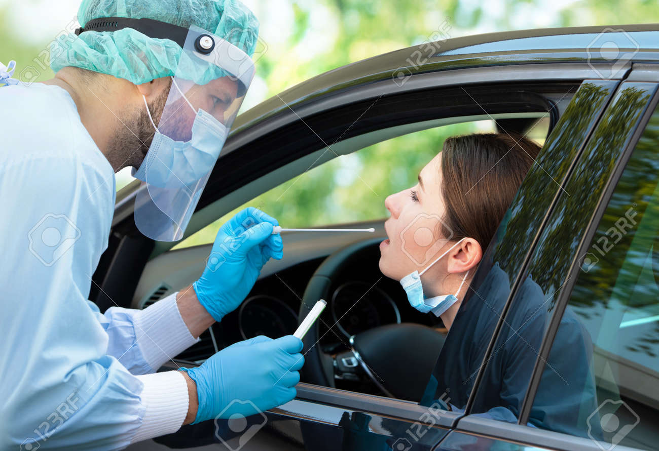 Woman getting tested at a coronavirus drive thru station by medical staff with PPE suit by throat swab. Health care drive thru service and medical concept - 153710901
