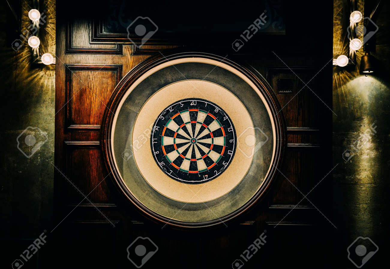 English style pub dart board with wooden backdrop and faded lights