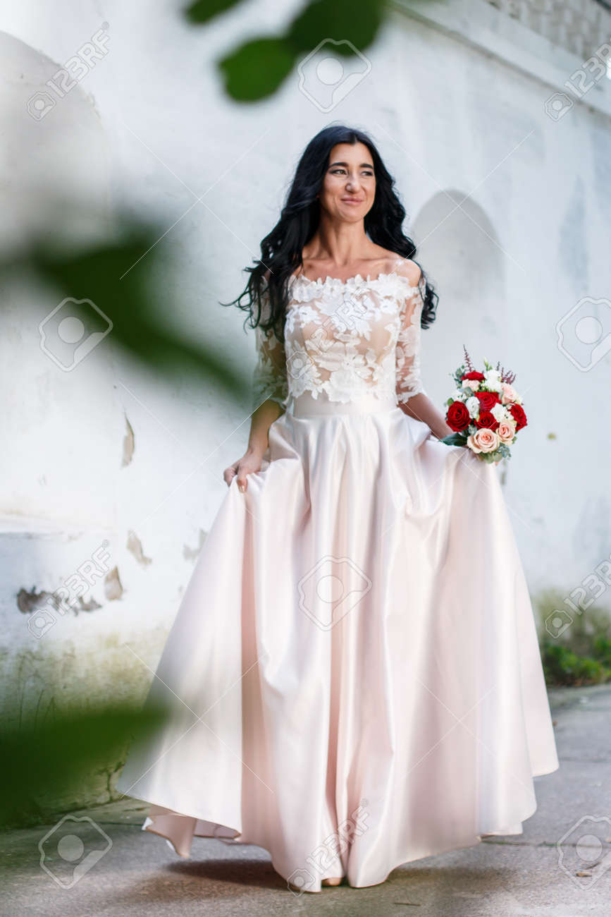 Beautiful Young Bride With Long Dark Hair And A Long White Wedding ...