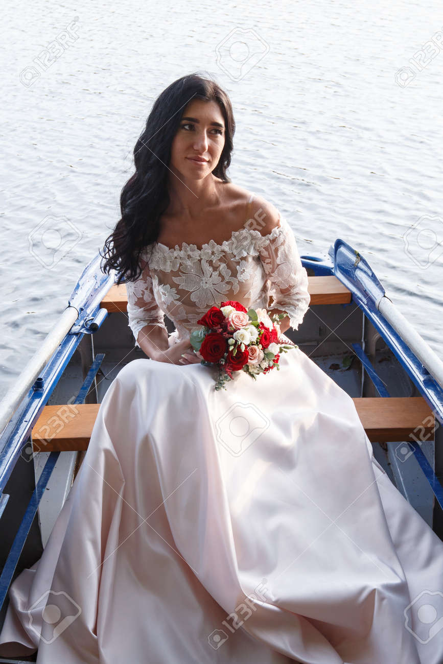 Young Beautiful Russian Bride With Long Hair Sitting In A Boat ...