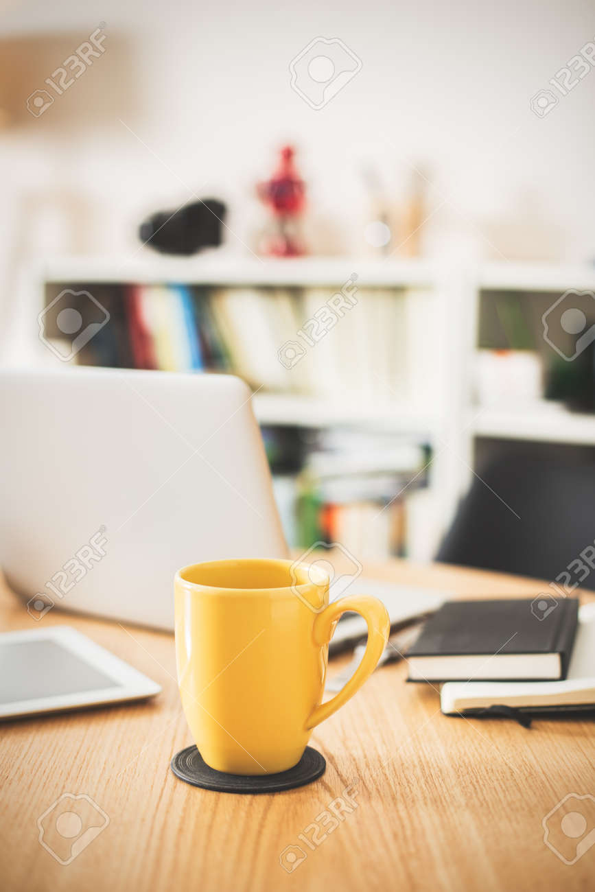 Detail of modern office with yellow cup of tea. - 39238603