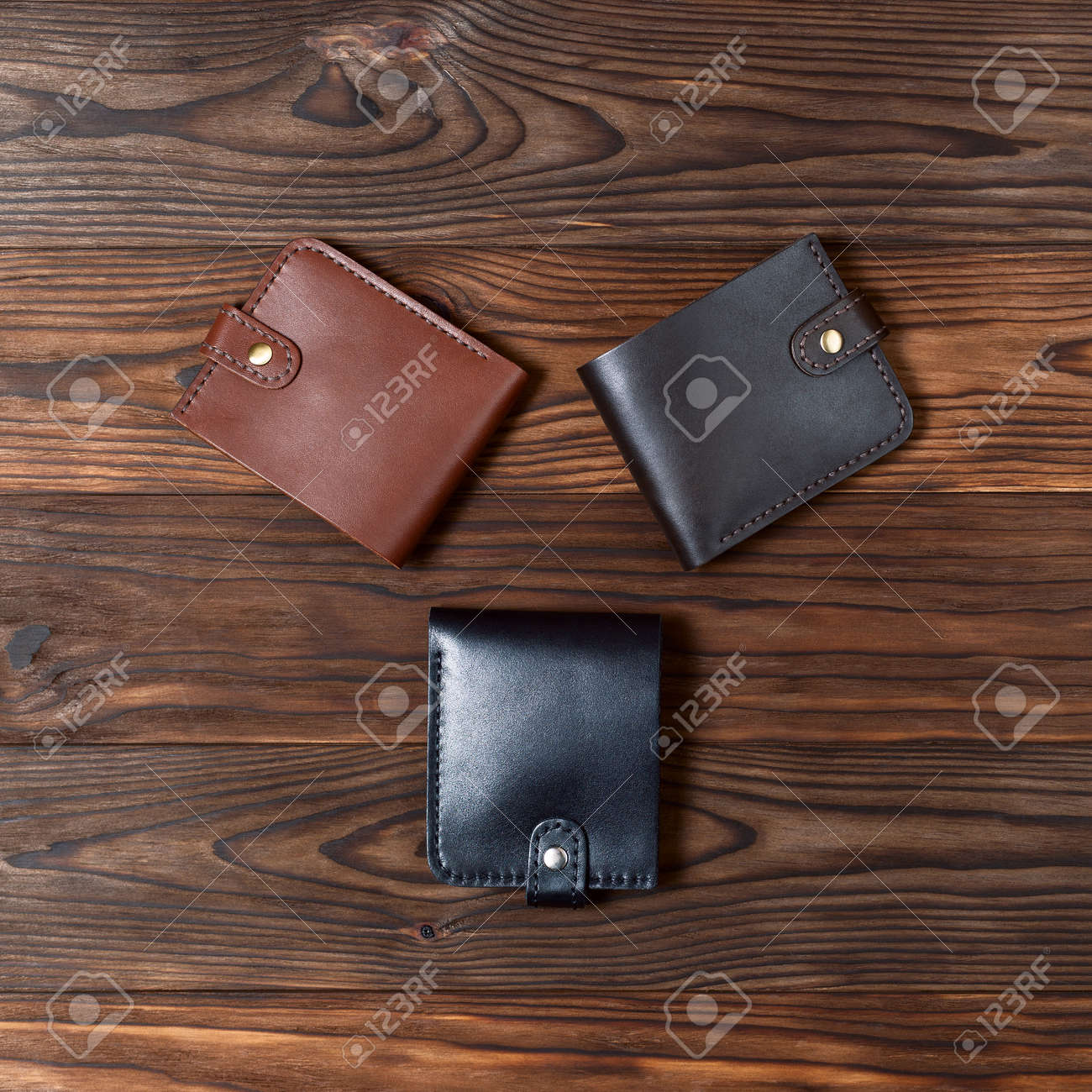 Three handmade leather gloss wallets on wooden textured background