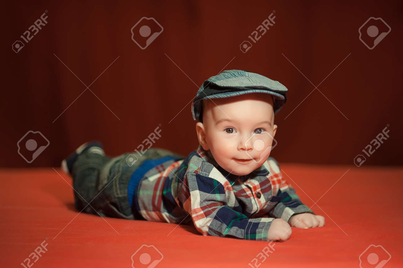 Cute Baby In A Tweed Flat Cap With A Red Background a03421e0907