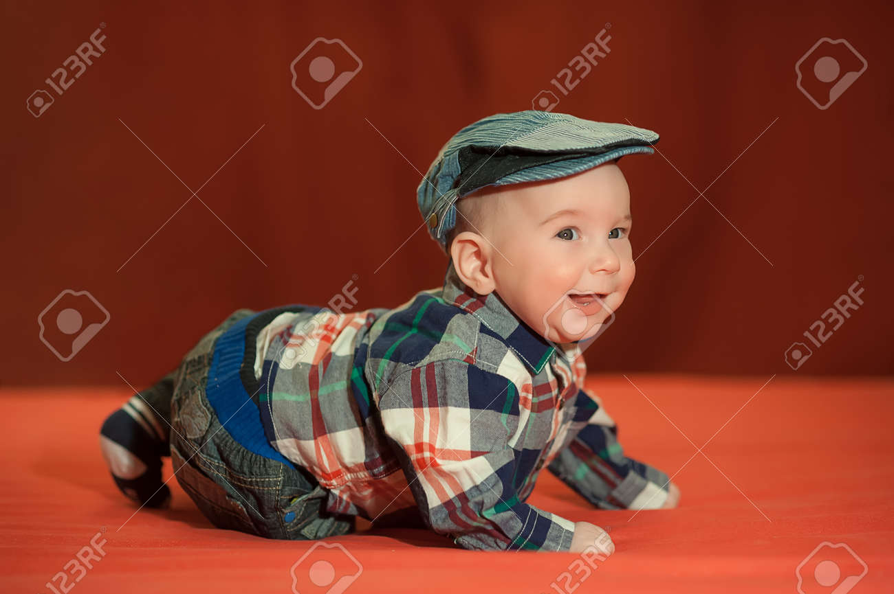 e9678b7c32e23 Cute Baby In A Tweed Flat Cap With A Red Background
